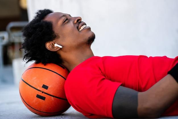 Portret van afro atleet man ontspannen en tot op de vloer na training buitenshuis