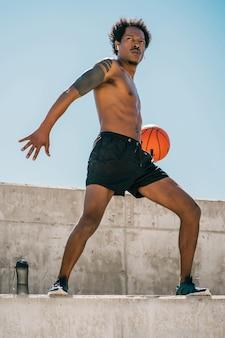 Portret van afro atleet man spelen en oefenen met basketbal bal buitenshuis. sport en een gezonde levensstijl.