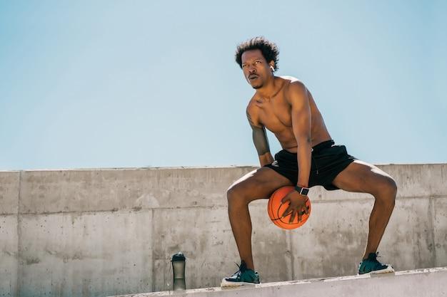 Portret van afro atleet man spelen en oefenen met basketbal bal buitenshuis