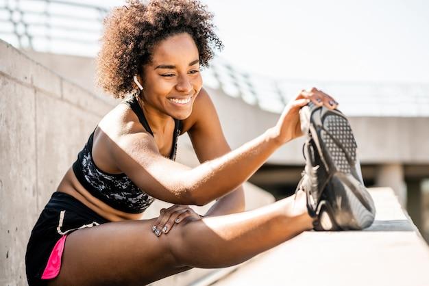 Portret van afro atleet vrouw die zich uitstrekt benen vóór oefening buitenshuis