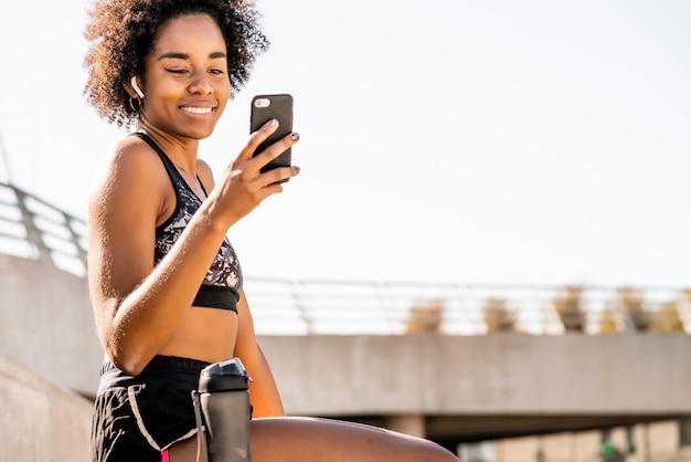 Portret van afro atleet vrouw met behulp van haar mobiele telefoon en ontspannen na het trainen buitenshuis