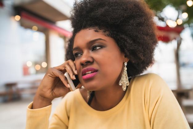 Portret van afro latijns-vrouw praten aan de telefoon zittend op coffeeshop. communicatie concept.