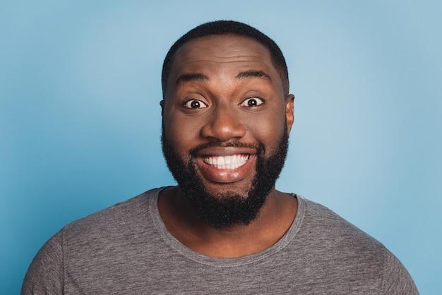 Portret van afro man met stralende glimlach geïsoleerd op blauwe achtergrond