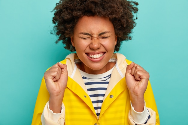 Portret van afro-meisje viert iets, glimlacht breed, toont witte tanden, gekleed in gestreepte trui en gele regenjas, roept vrolijk, geïsoleerd op blauwe achtergrond