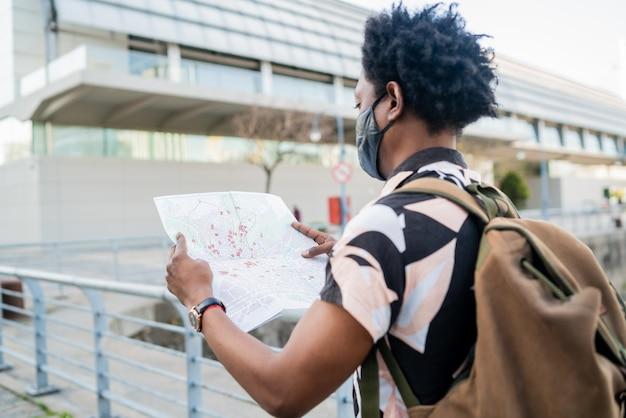 Portret van afro toeristenmens die beschermend masker draagt en richtingen op kaart zoekt