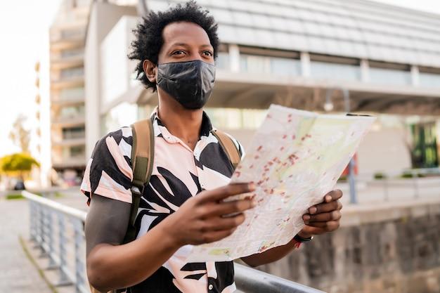 Portret van afro toeristische man met beschermend masker en op zoek naar een routebeschrijving op de kaart terwijl hij buiten op straat loopt. toerisme concept.