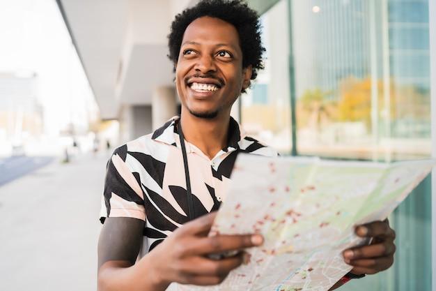 Portret van afro toeristische man op zoek naar een routebeschrijving op de kaart terwijl hij buiten op straat loopt.