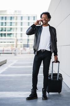 Portret van afro toeristische man praten aan de telefoon en koffer dragen tijdens het wandelen buiten op straat. toerisme concept.
