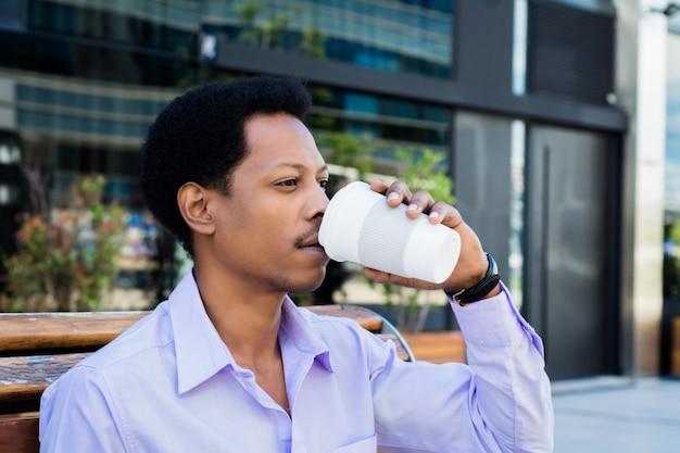 Portret van afro zakenman die een pauze neemt van het werk en buitenshuis een kopje koffie drinkt. bedrijfsconcept.