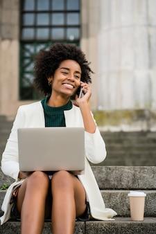 Portret van afro zakenvrouw praten aan de telefoon en met behulp van haar laptop zittend op de trap buiten