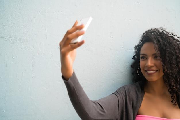 Portret van afrovrouw die selfies met haar mophile telefoon neemt tegen grijze muur. technologie concept.