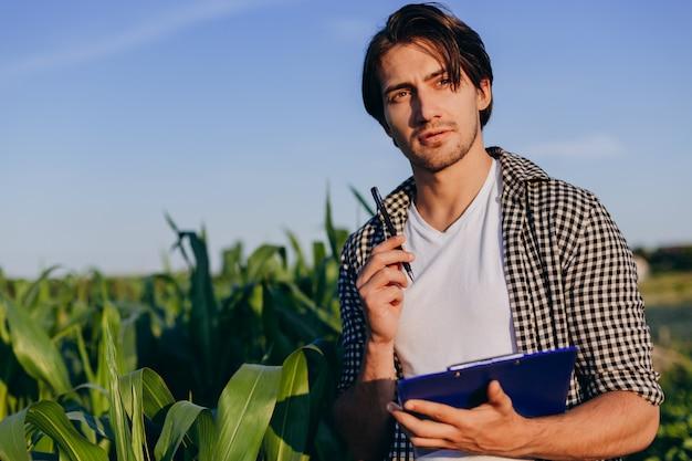 Portret van agronoom in een veld dat de opbrengst regelt en een notitie maakt