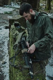 Portret van airsoft-speler in professionele apparatuur laadt een pistool met kogels in het bos.