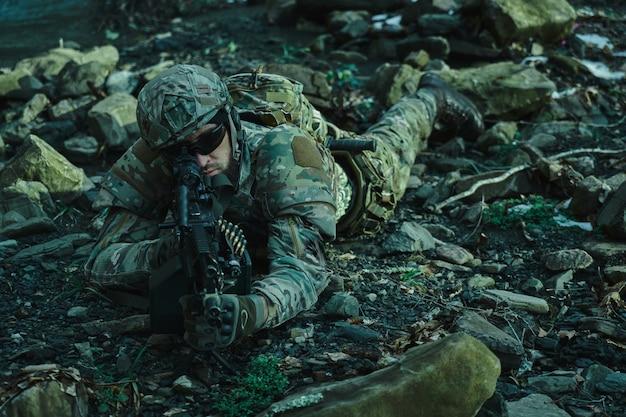 Portret van airsoft-speler in professionele uitrusting in helm die het slachtoffer met kanon in het bos beogen. soldaat met wapens in oorlog