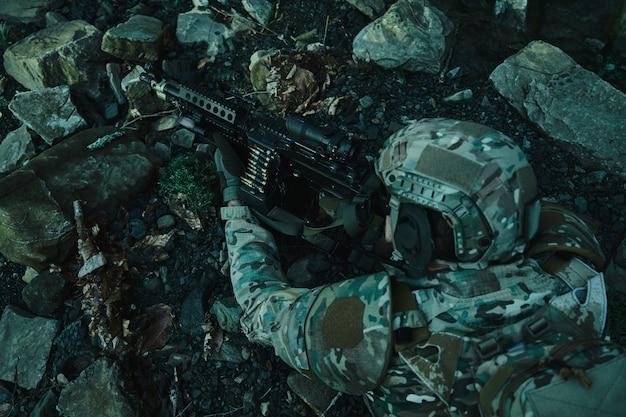 Portret van airsoft-speler in professionele uitrusting in helm die het slachtoffer met kanon in het bos beogen.
