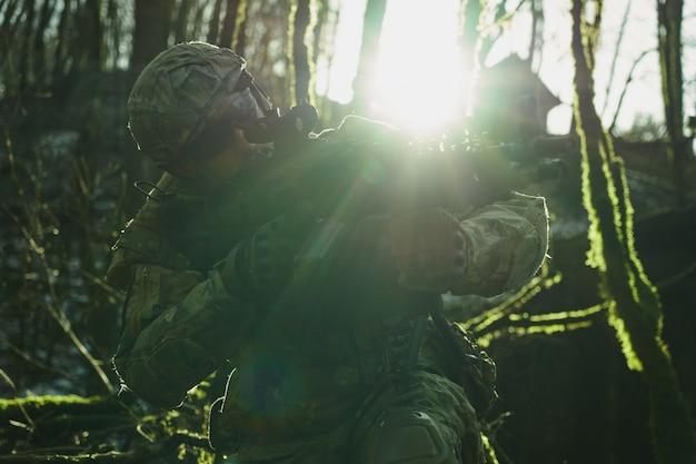 Portret van airsoft-speler in professionele uitrusting in helm gericht op slachtoffer met pistool in het bos. soldaat met wapens in oorlog
