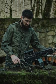 Portret van airsoft-speler in professionele uitrusting laadt een pistool met kogels in het bos. soldaat met wapens in oorlog