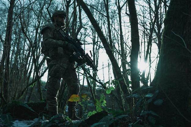 Portret van airsoft-speler in professionele uitrusting met machinegeweer in het bos. soldaat met wapens in oorlog