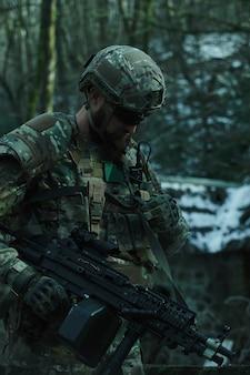Portret van airsoft-speler in professionele uitrusting met machinegeweer in het bos.