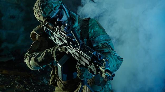 Portret van airsoft-speler in professionele uitrusting met machinegeweer in verlaten verwoeste gebouw. soldaat met wapens in oorlog in rook en mist