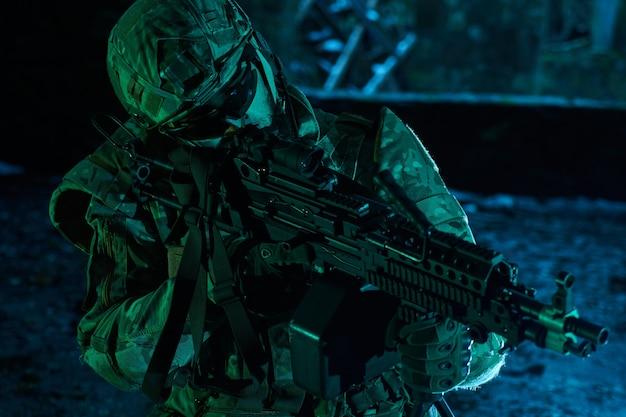 Portret van airsoft-speler in professionele uitrusting met machinegeweer in verlaten verwoeste gebouw. soldaat met wapens in oorlog