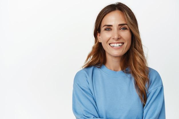Portret van ambitieuze en zelfverzekerde volwassen 30-er jaren vrouw, armen gekruist en gelukkig lachend naar voren, vooruitkijkend, staande tegen een witte muur