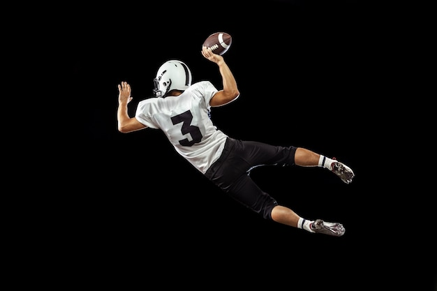 Portret van american football-speler in sportuitrusting geïsoleerd op black