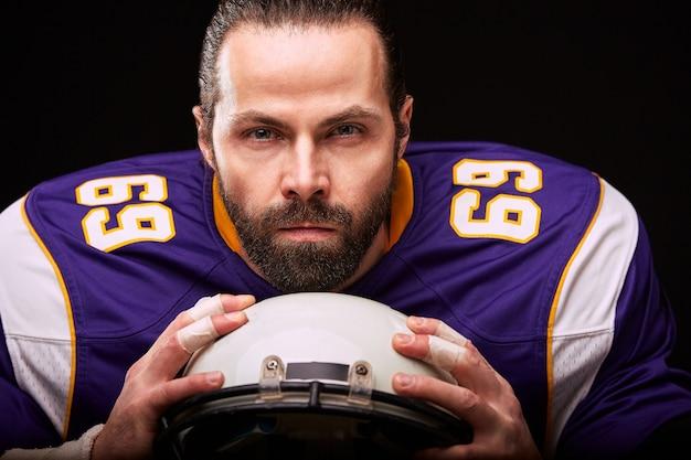 Portret van american football-speler met helm in de hand close-up op zwarte achtergrond