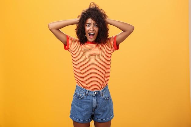 Portret van anafro kapsel vrouw handen houden op haar schreeuwen van shock over oranje muur