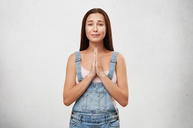 Portret van angstaanjagende vrouw draagt een wit overhemd en een denim overall, houdt de handpalmen bij elkaar en gaat huilen terwijl ze om vergeving vraagt. jonge donkerbruine vrouw met sombere blik die over witte muur wordt geïsoleerd