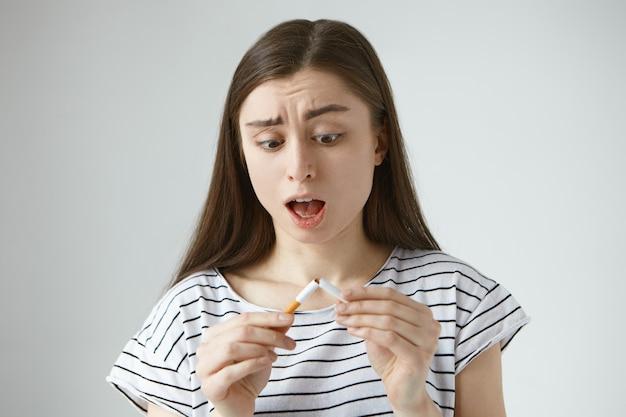 Portret van angstig geschokt jonge brunette vrouw die mond opent van verbazing, geschrokken uitdrukking heeft, kijkend naar de laatste sigaret die net in haar handen brak, paniek en wanhopig voelde