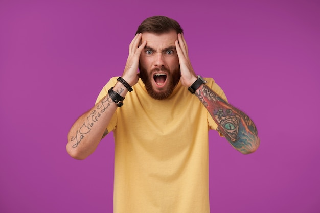 Portret van angstige bue-eyed getatoeëerde brunette man met baard bang op zoek met brede mond geopend en houdt zijn hoofd met opgeheven handen, geïsoleerd op paars
