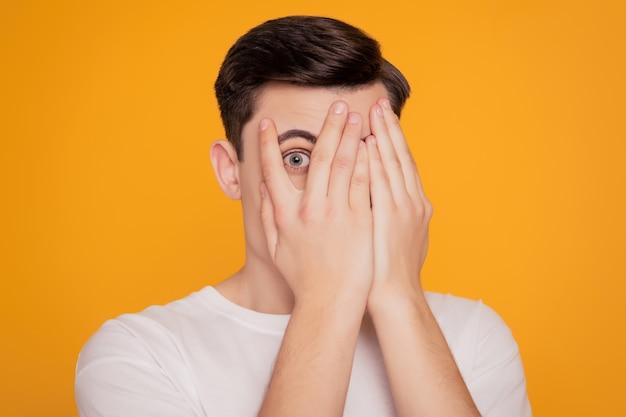 Portret van anonieme man handen bedekken gezicht gluren peering ogen op gele achtergrond