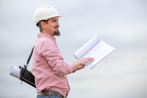 Portret van architect aan het werk met helm in een bouwplaats, leest het plan, papieren projecten