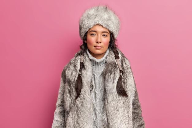 Portret van arctische woaman met twee staartjesjurken voor koud klimaat draagt grijze bontjas en hoed die over roze muur wordt geïsoleerd
