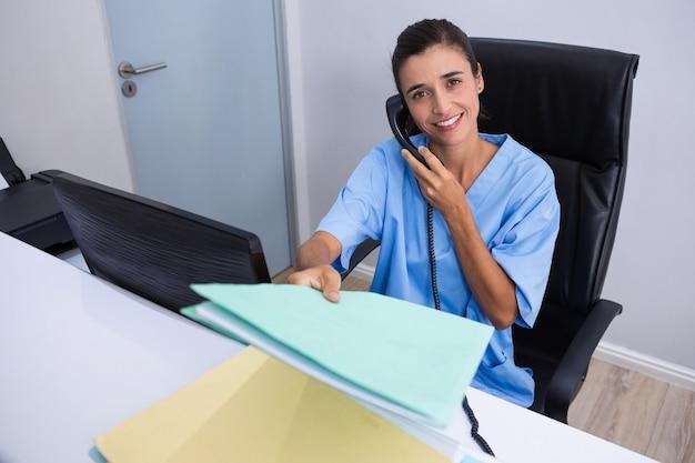 Portret van arts die dossier tijdens het gesprek op telefoon houdt