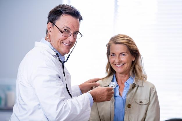 Portret van arts die een vrouwelijke patiënt onderzoekt