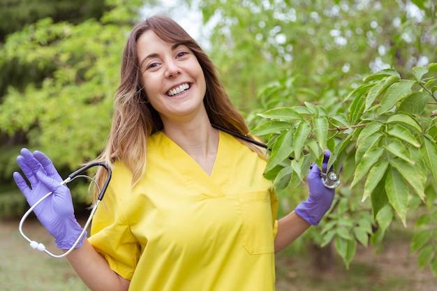 Portret van arts die gelukkig met haar handen een stethoscoop houdt