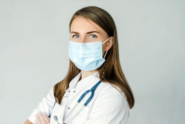Portret van arts die medisch masker dragen en handschoenen die op grijze achtergrond wordt geïsoleerd. detailopname
