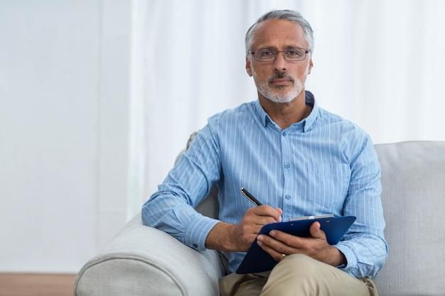 Portret van arts die op een klembord thuis schrijft