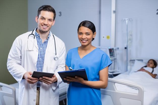 Portret van arts en verpleegster die digitaal tablet en klembord gebruiken