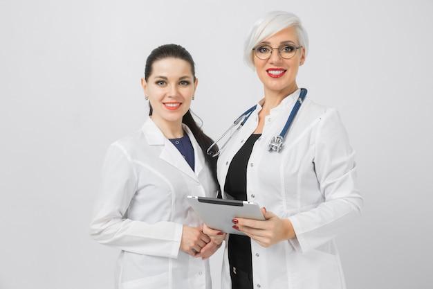Portret van arts en verpleegster met tablet in handen op witte achtergrond wordt geïsoleerd die