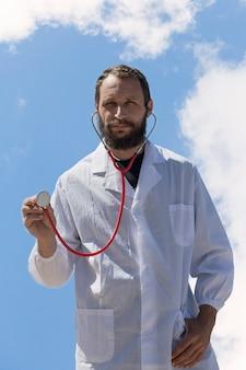 Portret van arts met stethoscoop in oor luister aandachtig naar je. amerikaanse knappe bebaarde man op blauwe hemelachtergrond. russische blanke brutale man in een witte jas. behandeling in israël