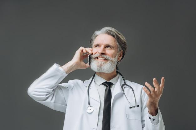 Portret van arts sensor op grijze muur. grijsharige senor arts gekleed in witte jas praten aan de telefoon.