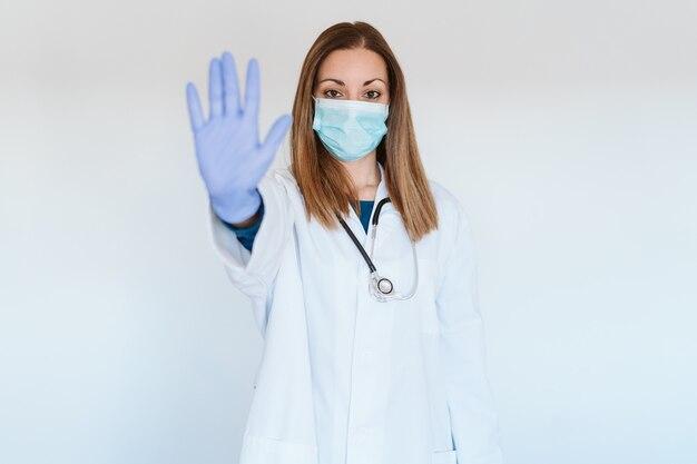 Portret van arts vrouw met beschermend masker en handschoenen binnenshuis. een stopbord maken met de hand. corona-virus concept