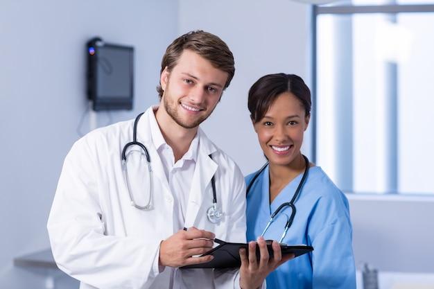 Portret van artsen die bespreking op klembord hebben