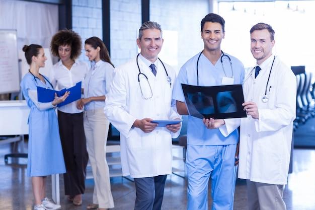 Portret van artsen die een röntgenstraal houden en in het ziekenhuis glimlachen