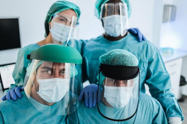 Portret van artsen die naar de camera kijken in het laboratoriumziekenhuis tijdens de uitbraak van het coronavirus - focus op het gezicht van de man linksonder