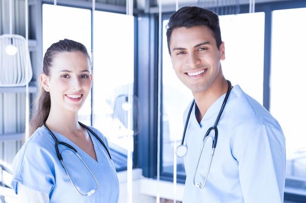 Portret van artsen die zich en bij camera in het ziekenhuis glimlachen verenigen
