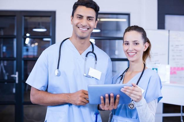 Portret van artsen gebruikend digitale tablet en glimlachend in het ziekenhuis